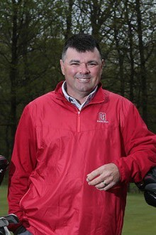 Coach Haverland poses on golf course.