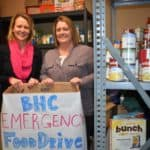 BHC staff members hold a food drive donation box in the pantry