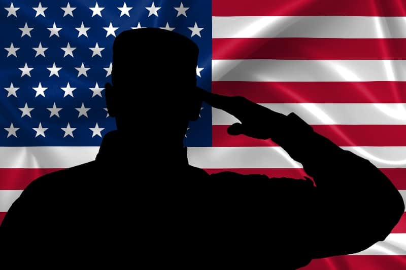 silhouette of soldier saluting with U.S. flag in background