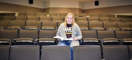smiling college student sitting in auditorium with open textbook