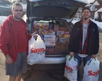 2 men holding plastic bags of groceries & lots of groceries in back of SUV