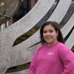 student wearing BHC East Campus shirt stands in front of a sculpture