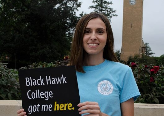 student with sign that reads Black Hawk College got me here at Iowa State University