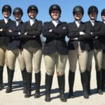 8 people wearing black riding helmets, black jackets, tan pants & black boots
