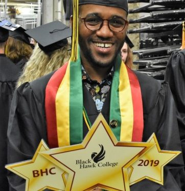Graduate wearing black cap and gown holding BHC 2019 sign