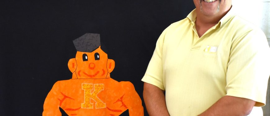 Kewanee High School teacher standing in front of a quilt featuring the school's mascot, a boilermaker