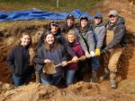 8 college students standing in soils pit