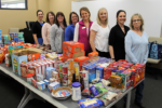 women standing behind a table filled with food pantry items