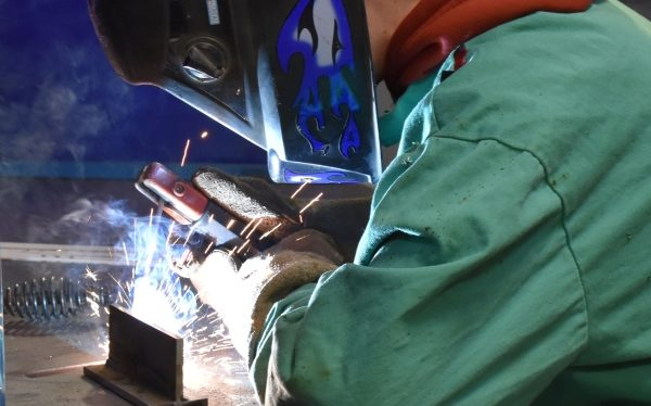 student welding and wearing protective equipment