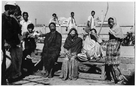The morning after the Bhopal gas disaster people sit with covered eyes