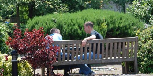 Photograph of keyworker and client sitting on bench