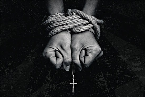 Christian persecution - bound hands holding a cross