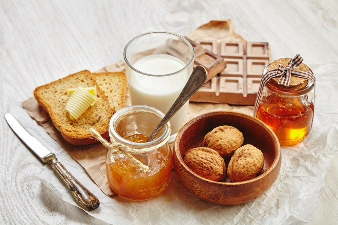Side view of breakfast set with chocolate walnuts in wooden bowl jam honey in gift jar dry toast bread butter and milk. Everything on craft paper and vintage knife and spoon with patina.