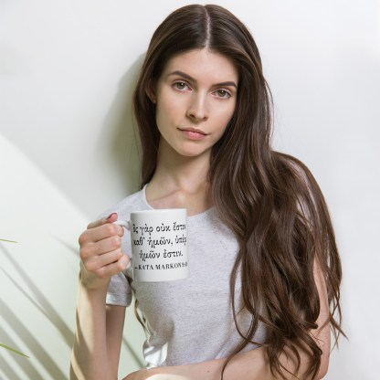 Woman holding 11 oz coffee mug with Biblical Greek Bible verse on front (Mark 9:40)