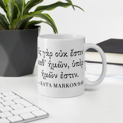 11 oz coffee mug (on desk) with Biblical Greek Bible verse on back (Mark 9:40)