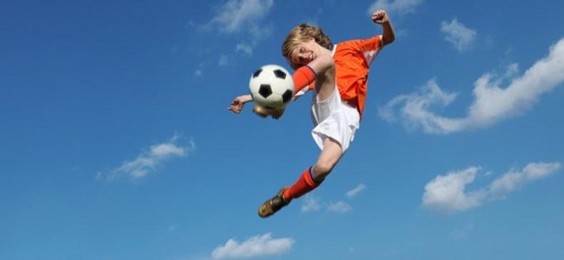 junge spielt Fussball, Luftsprung
