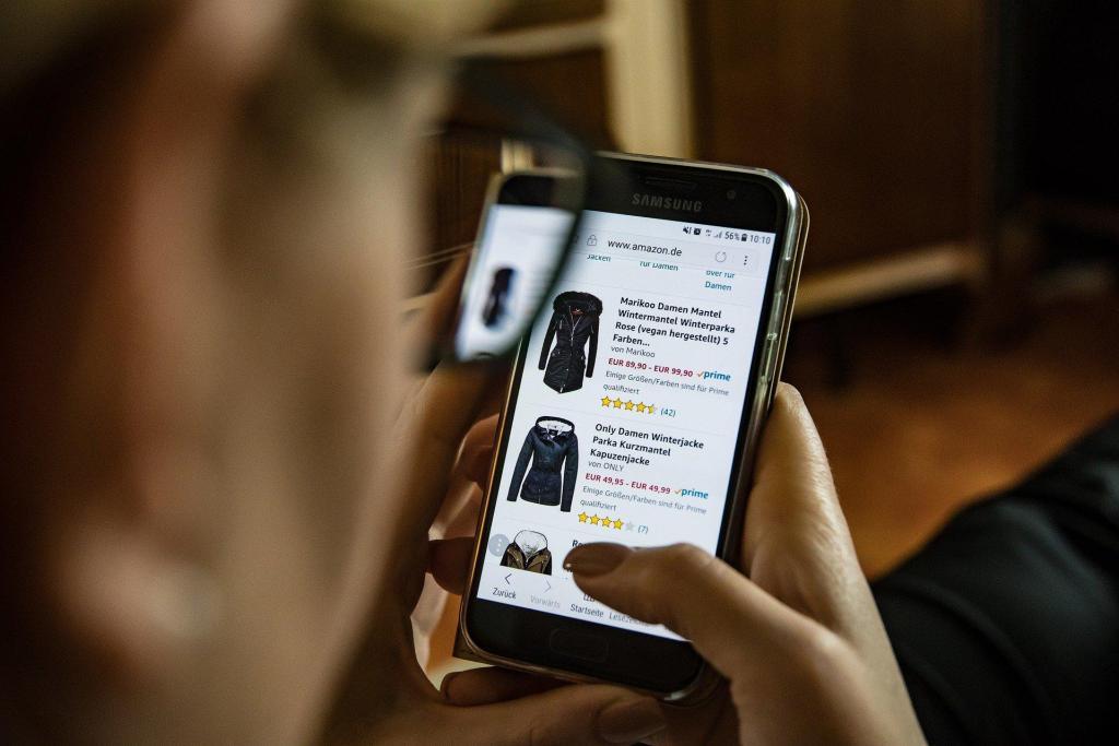 Frau shoppt mit Smartphone auf mobiler Amazon-Webseite und betrachtet verschiedene Mäntel