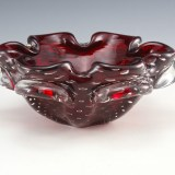 Eye-catching vintage cased ruby glass ashtray bowl hand-made in the Mid-20th Century. Blown in ruby red cased in colorless with trapped bubbles between the layers.