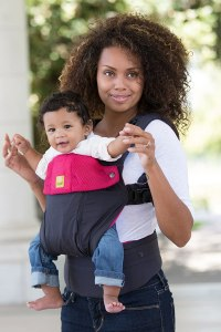 Model with baby in a berry/charcoal Lillebaby carrier