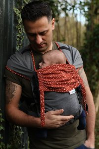 Man carrying a baby in a red and grey Mamaruga Zensling