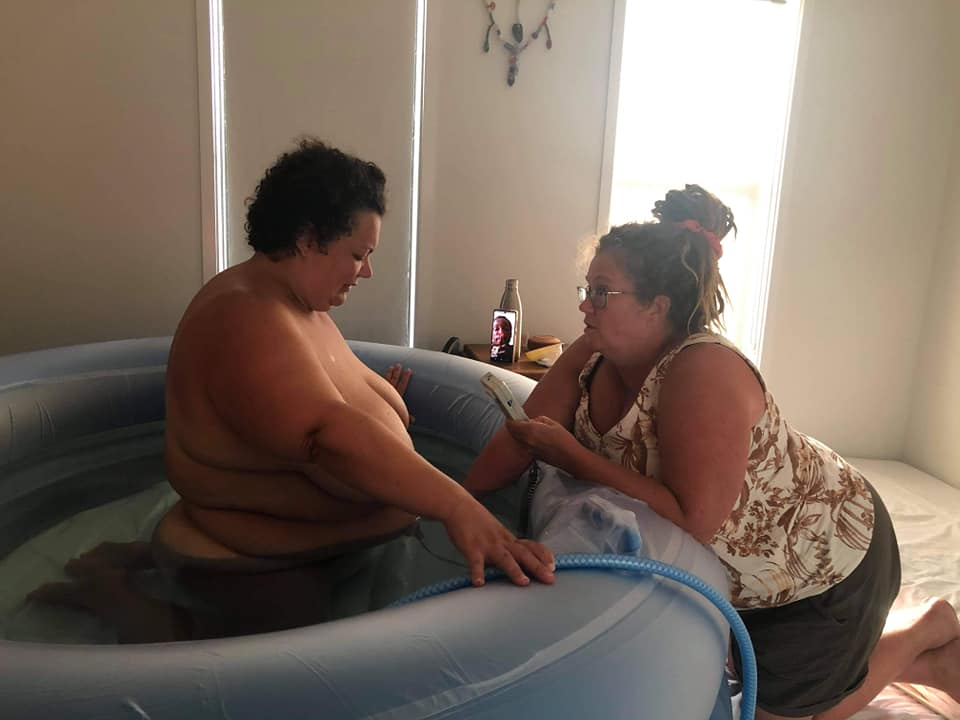 Deb the midwife using a handheld doppler to monitor Winnie's heartbeat while Amy is in the pool. Amy's home waterbirth story