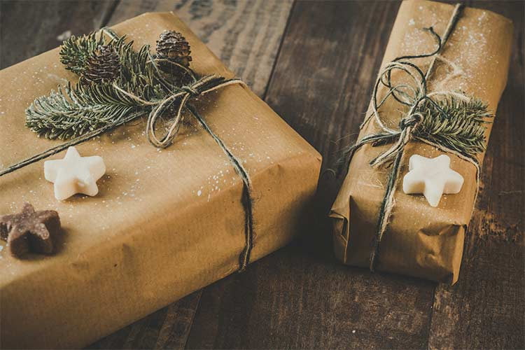 Brown paper wrapped packages tied up with strings and green foliage