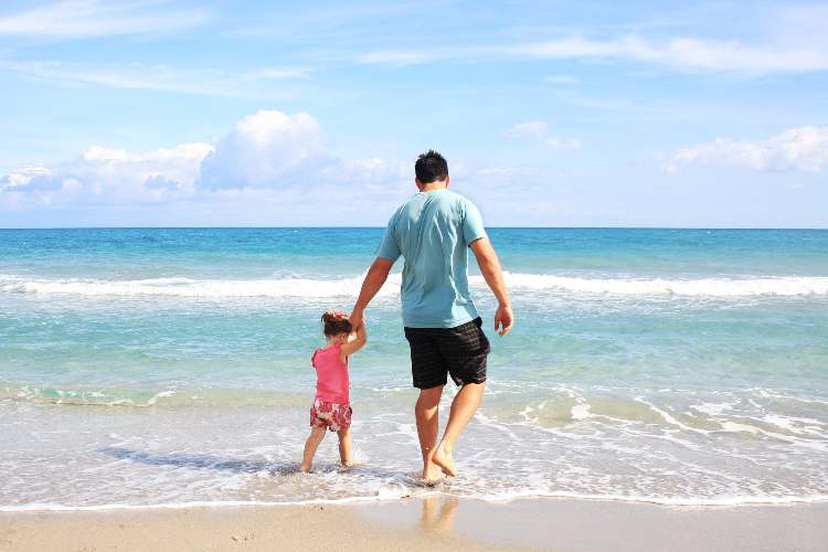 father paddling walking hand in hand with little girl on the beach