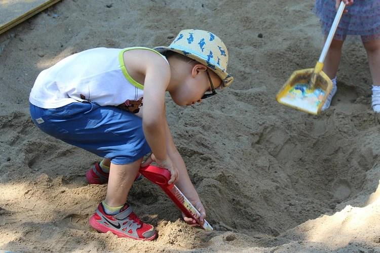 young boy improving teamwork skills in a sandpit