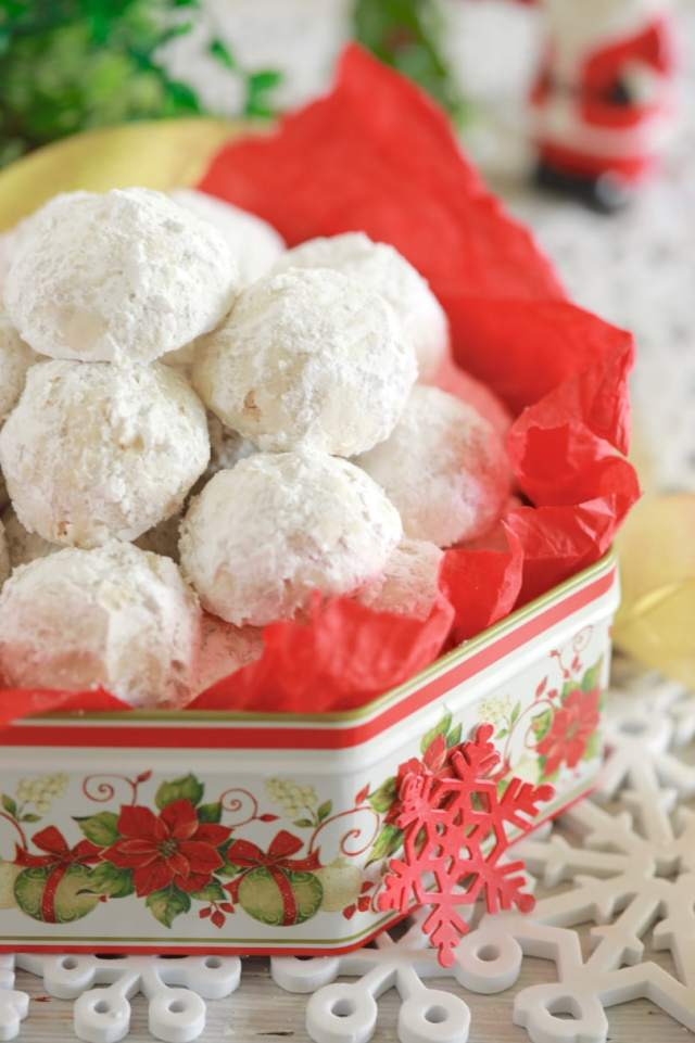 Classic Snowball Cookies, or Christmas Snowball Cookies, baked and displayed in a decorative tin, covered in powdered sugar.