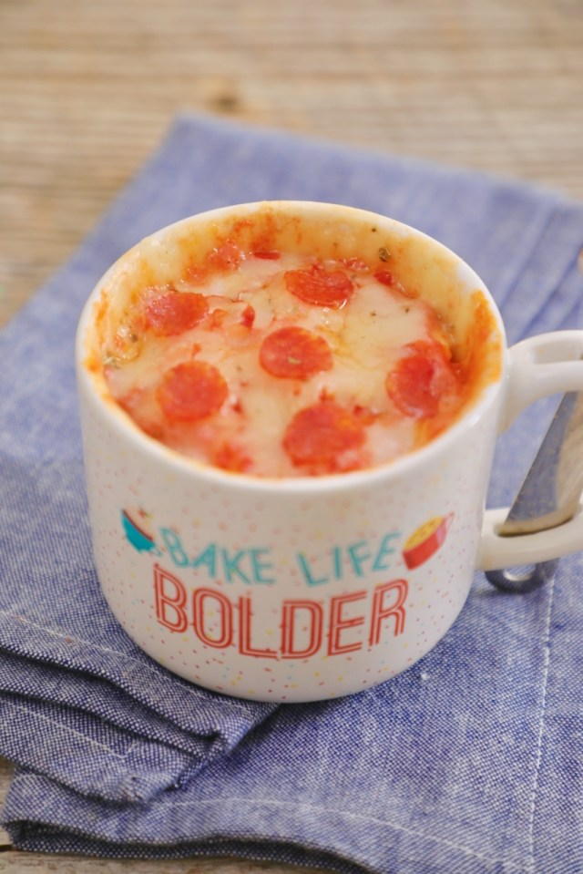 A single serving pizza made in the microwave and baked in a mug, topped with cheese and pepperonis.