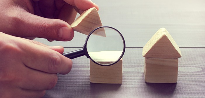 magnifying glass looking into wooden blocks shaped like houses