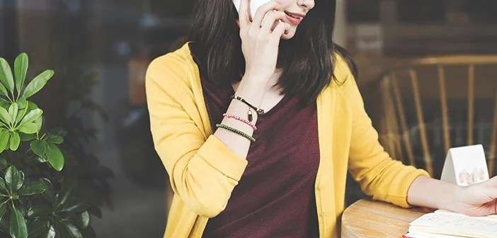 woman in maroon shirt and yellow sweater talking on a cell phone while going over notes on a notepad