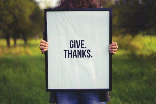vrouw met bord 'give thanks', biddag en dankdag