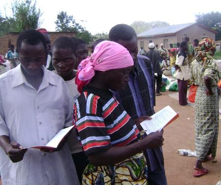 Op de markt proberen een aantal Kabwa-mensen voor het eerst hun taal te lezen.
