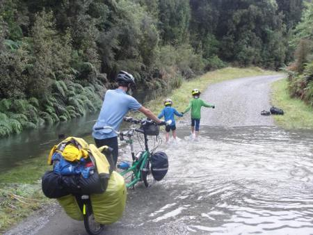 Tandem bike fording a small river in New Zealand