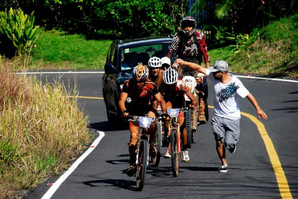 Stage winner Manny Prado gets a cold shower while riding a stretch of hot pavement. Photo: J. Andrés Vargas