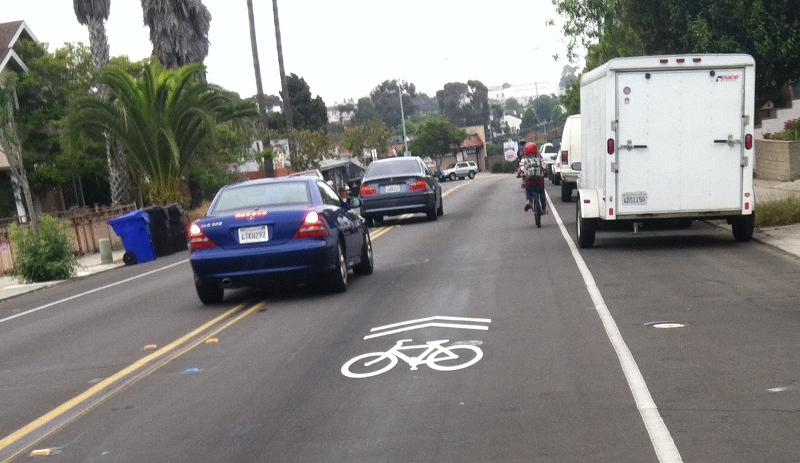 drivers pass a bicyclist on a sharrow-marked street