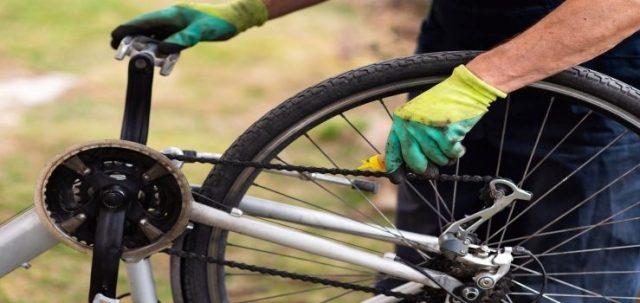 una persona que lubrica la cadena de su bicicleta