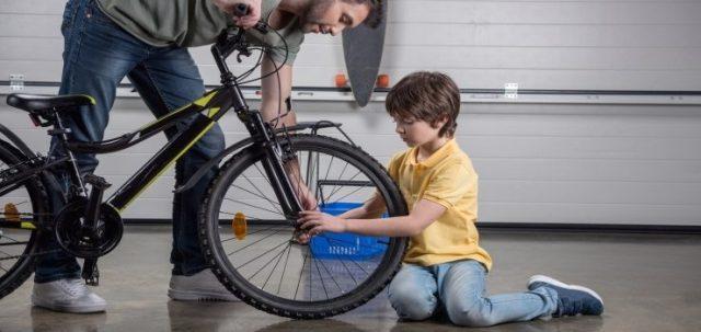 padre e hijo revisando la bicicleta