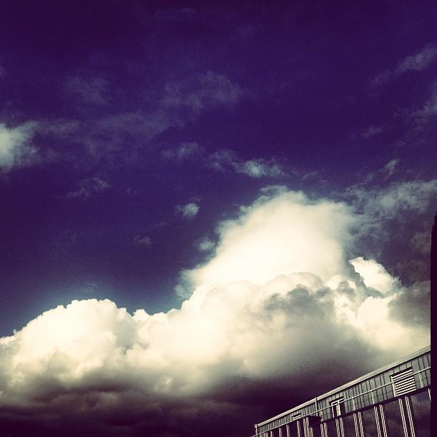 Wolkenberge vor dem Fenster und Arbeitsberge auf dem Schreibtisch…