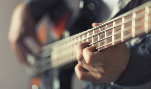 Close up image of the neck of a bass guitar.