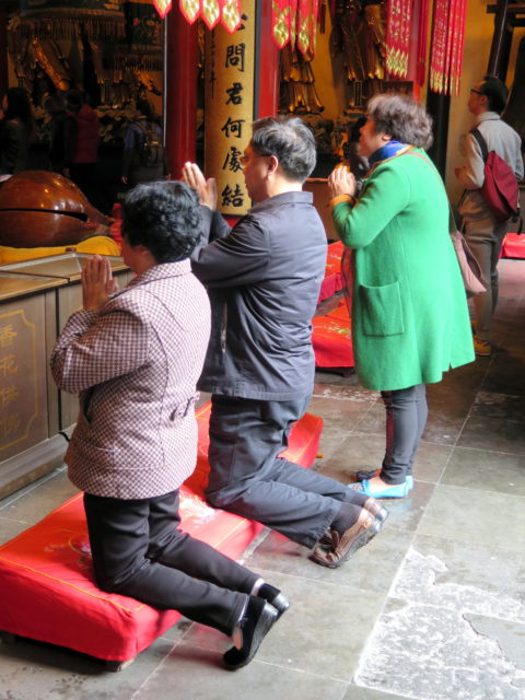 There is always lots of praying going on at Buddhist temples. Jade Buddha Temple, Shanghai, China, Asia.