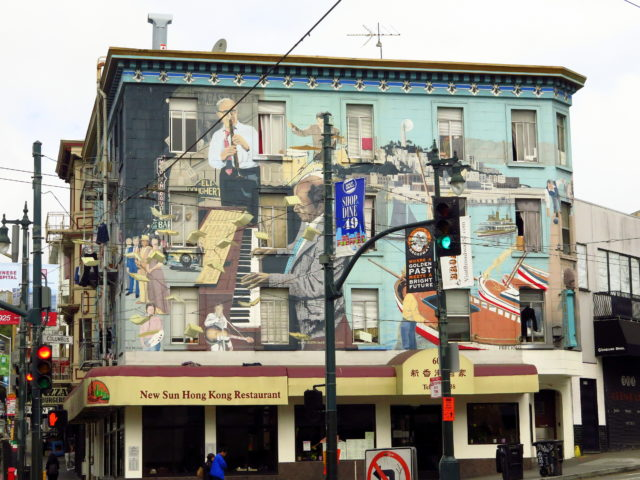 """The east side of the mural. On the right are scenes of North Beach and Italian fishing boats. On the Barbary Coast corner, a jazz trio plays: Benny Goodman on clarinet, Gene Krupa on drums, and Teddy Wilson on piano. Maybe you can see open books hanging from wires in front of the mural. That is an artwork called """"Language of the Birds"""". San Francisco, United States, North America."""