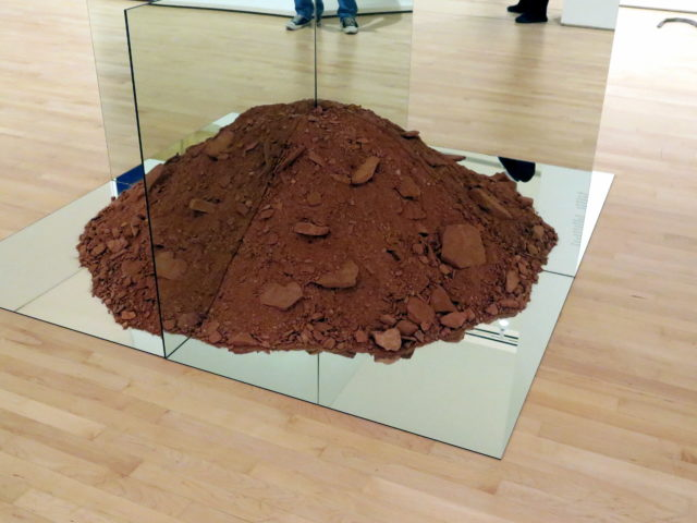 """Dirt. More specifically, a pile of dirt with mirrors going through it to create 4 quadrants of dirt. More specifically, """"Nonsite (Essen Soil and Mirrors)"""" by Robert Smithson, 1969. Robert died in a plane crash at 35 4 years later. (Sorry for my sneakers in the reflection.) SFMOMA, San Francisco, United States, North America."""