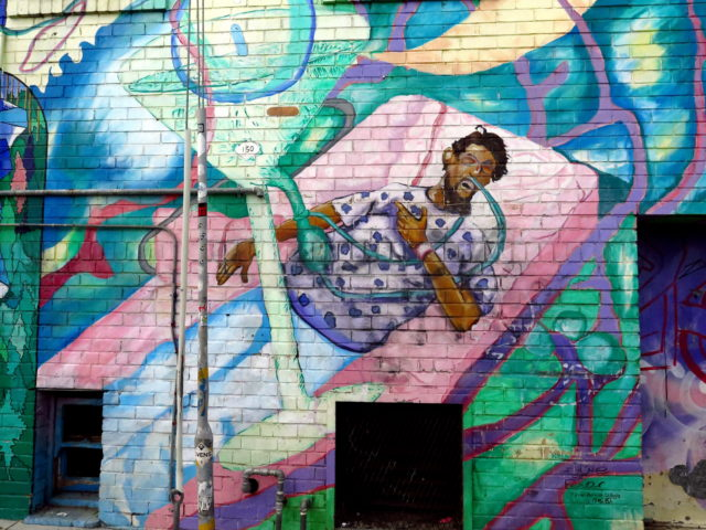 "In this scene from the ""Hope for the World Cure"" mural, an AIDS patient receives a figurative cocktail of AIDS medications. San Francisco, United States, North America."