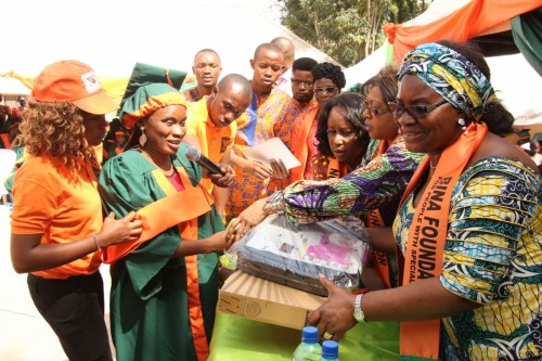 A volunteer, Lady Bene nwankwo gives certificate of Profiecncy and a brand new laptop to a blind student