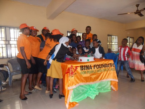 Children cut their Christmas Party cake with Bina Foundation Staffs