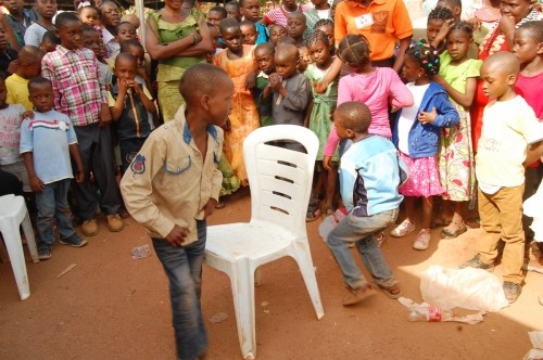 Orphans and vulnerable children doing a chair dance during the christmas party