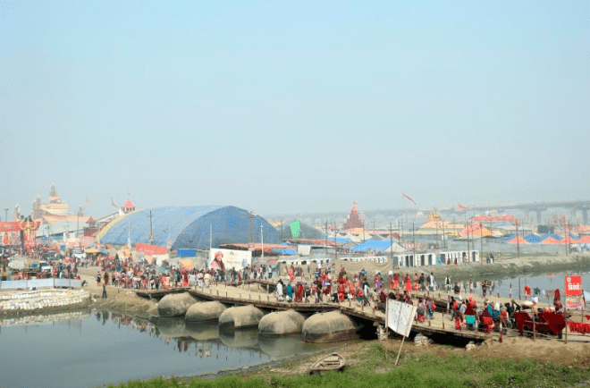 People walking on the pontoon bridge to reach the mela