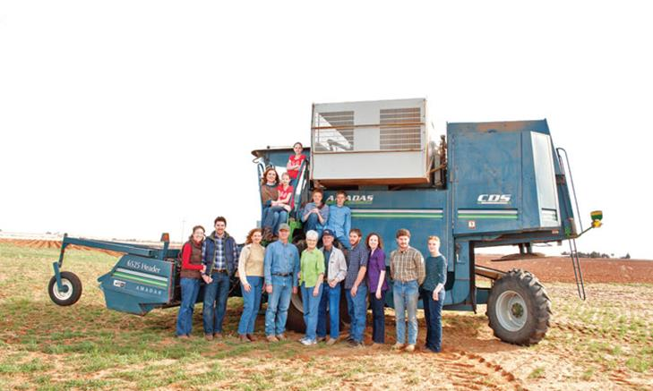Eddie and Peggy Bingham, Cliff and Betty Bingham, and their children in front of a peanut combine at Bingham Organic Farm.